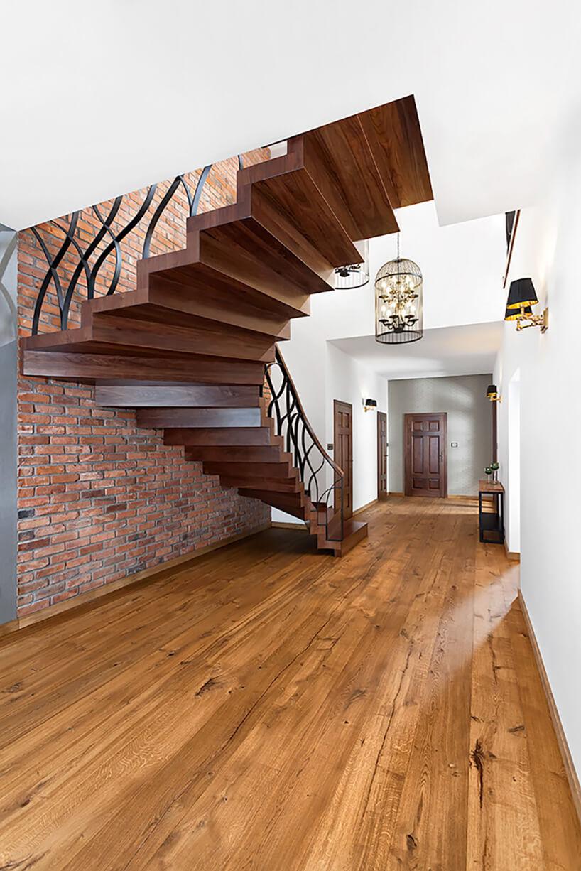 zakręcone schody zdrewna przy ścianie zcegły