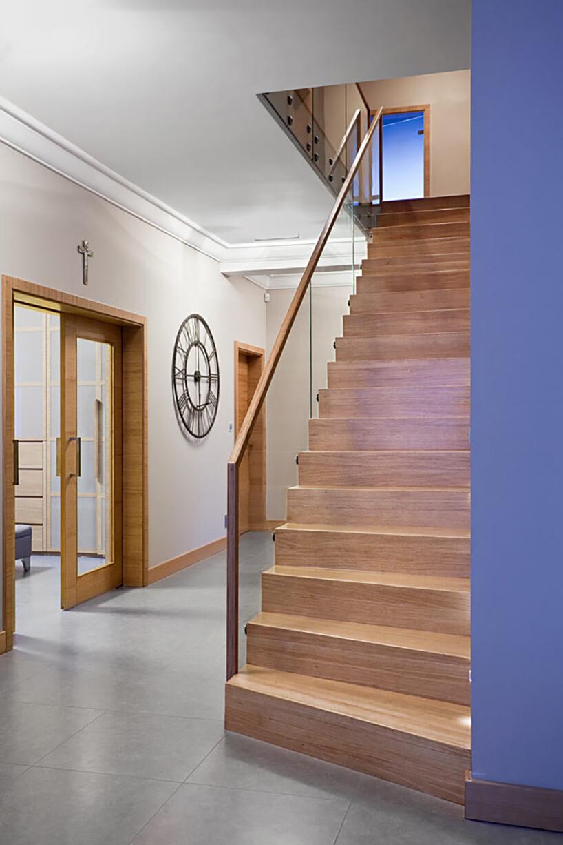 schody zjasnego drewna ze szklaną barierką