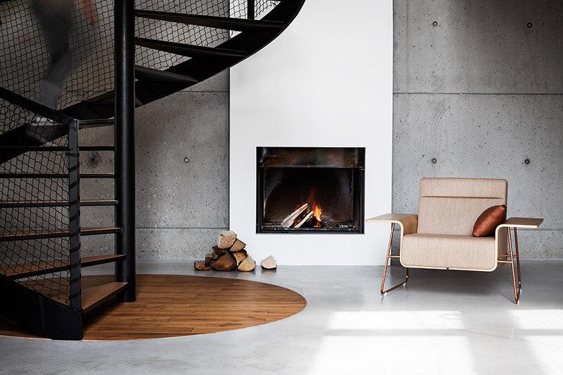 fotel przy kominku wbetonowym wnętrzu przy czarnych schodach