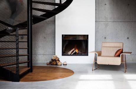 fotel przy kominku w betonowym wnętrzu przy czarnych schodach