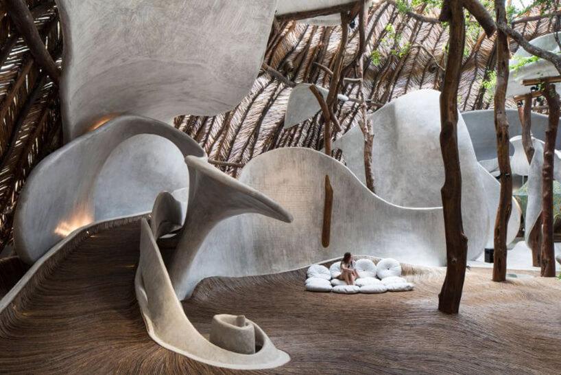 przestrzeń muzeum zdrewnianą podłogą zbiałymi dużymi elementami pod drewnianym dachem podpartego drewnianymi filaramii
