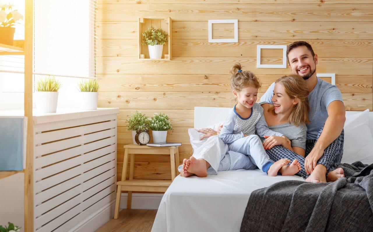 szczęśliwa rodzina siedząca na dużym łóżku na tle drewnianej ściany ozdobionej ramkami ikwiatami