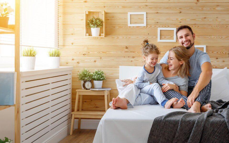 szczęśliwa rodzina siedząca na dużym łóżku na tle drewnianej ściany ozdobionej ramkami i kwiatami w białych doniczkach