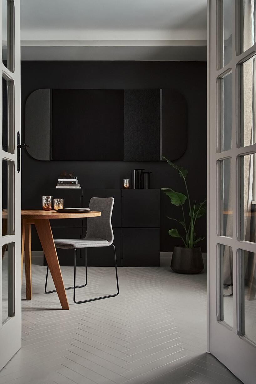 elegancka czarna aranżacja salonu zszarą podłogą drewnianym stołem zszarym krzesłem na tle czarnej komody