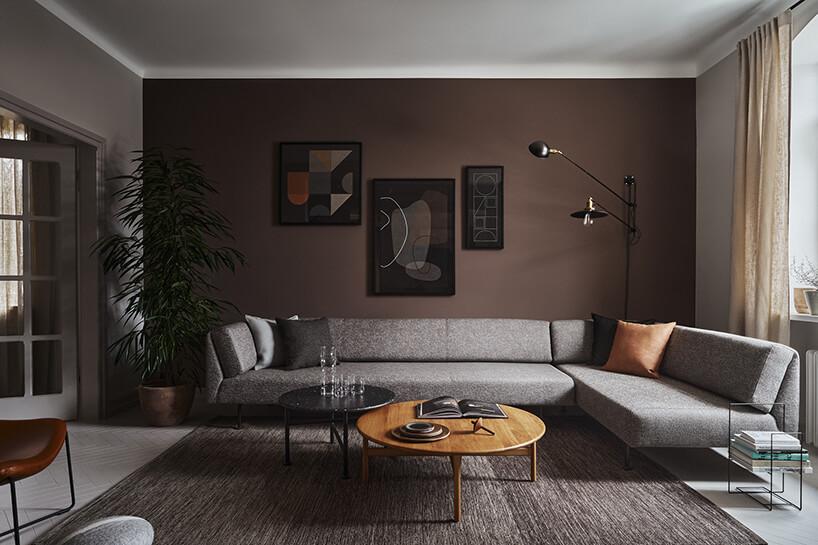 elegancki ciemny salon zdużą szarą narożną sofą na przy dwóch niskich okrągłych stolikach na szarym dywanie