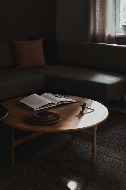 niski drewniany stolik na szarym dywanie na tle szarej narożnej sofy
