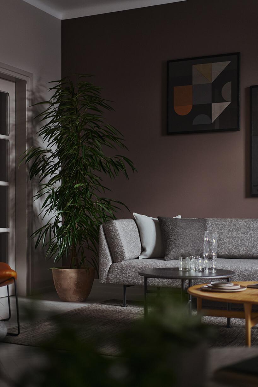 dwa niskie stoliki na tle szarej sofy ba metalowych czarnych nogach obok wysokiego kwiatka wceramicznej donniczce
