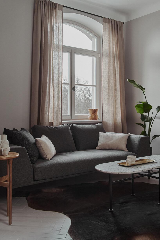 ciemno szara sofa zgrubymi oparciami na białej podłodze znieregularnym ciemnym dywanie