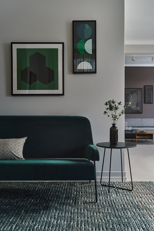 ciemno zielona sofa obok małego okrągłego stolika na dywanie zdużych nici