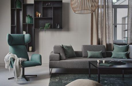 zielony fotel na czarnej nodze obok szarej sofie z niskim oparciem przy czarnym stoliku