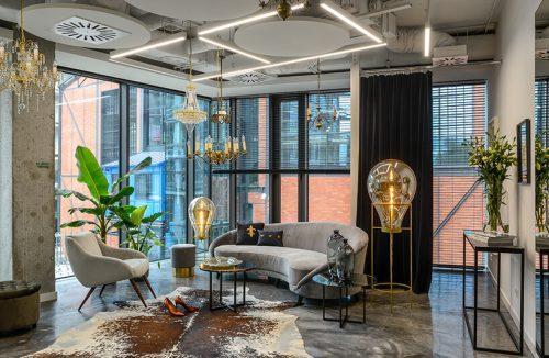 nowe atelier Paprocki & Brzozowski szara sofa obok dwóch wyjątkowych lamp na szarej kamiennej podłodzekamienna podłoga