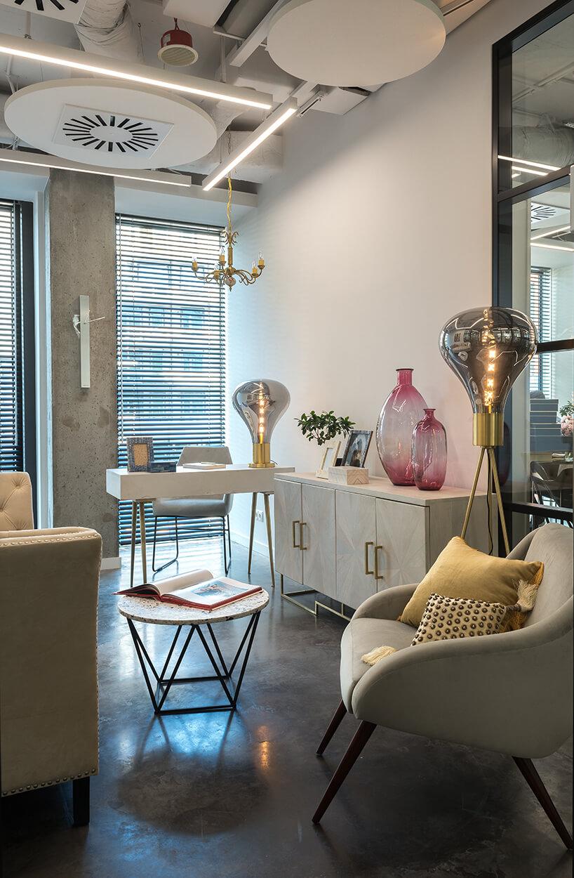 nowe atelier Paprocki & Brzozowski aranżacja białego wnętrza zbiałą szafką ze złotymi elementami na tle małego białego biurka znowoczesną złota lampą