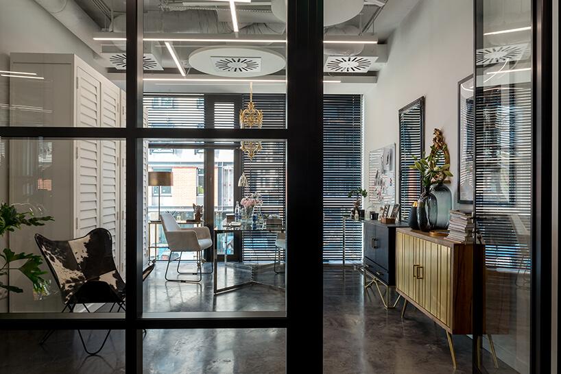 nowe atelier Paprocki & Brzozowski aranżacja wnętrza zciemną podłogą brązowo złotą szafką ifotelem wbrązowo białe łaty