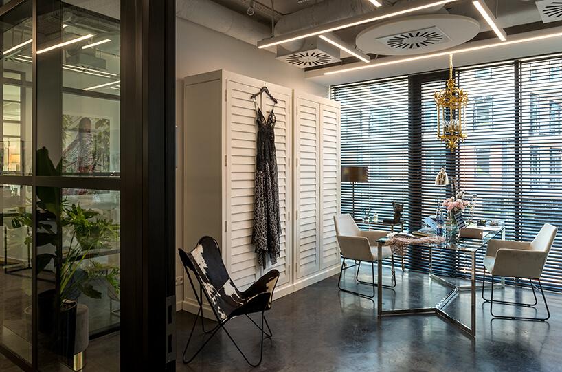nowe atelier Paprocki & Brzozowski szklany stolik na srernych nogach zdwoma białymi fotelami obok dużej białej szafy