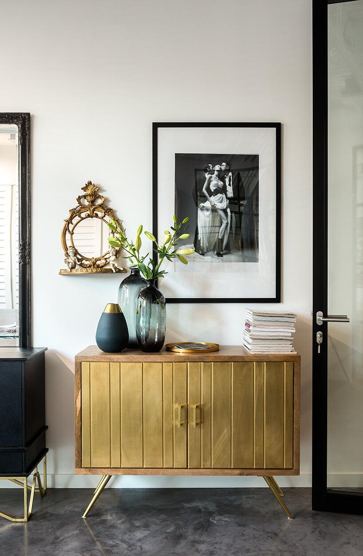 nowe atelier Paprocki & Brzozowski elegancka szafka ze złotymi drzwiczkami na złotych nogach na ciemnej kamiennej podłodze