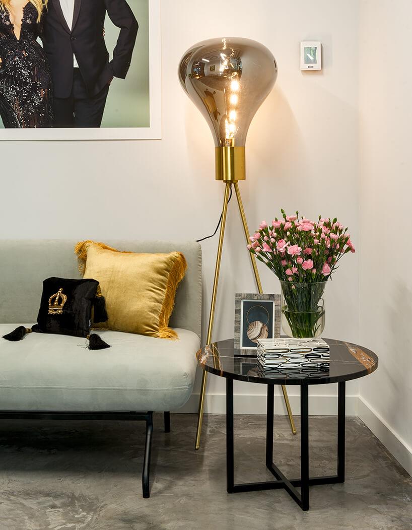 nowe atelier Paprocki & Brzozowski efektowna wysoka złota lampa wkształcie żarówki obok szarego siedziska obok małego czarnego stolika