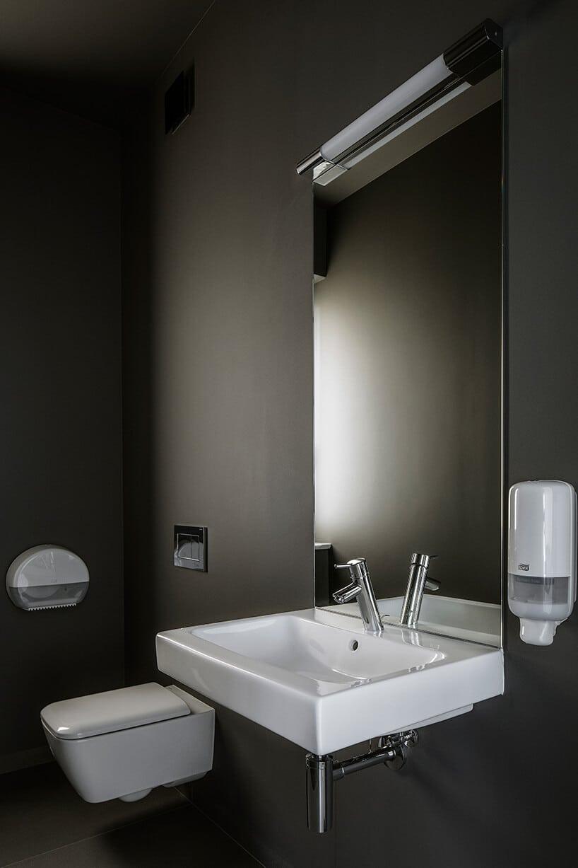 ciemne wnętrze toalety zjasną białą armaturą pod lustrem