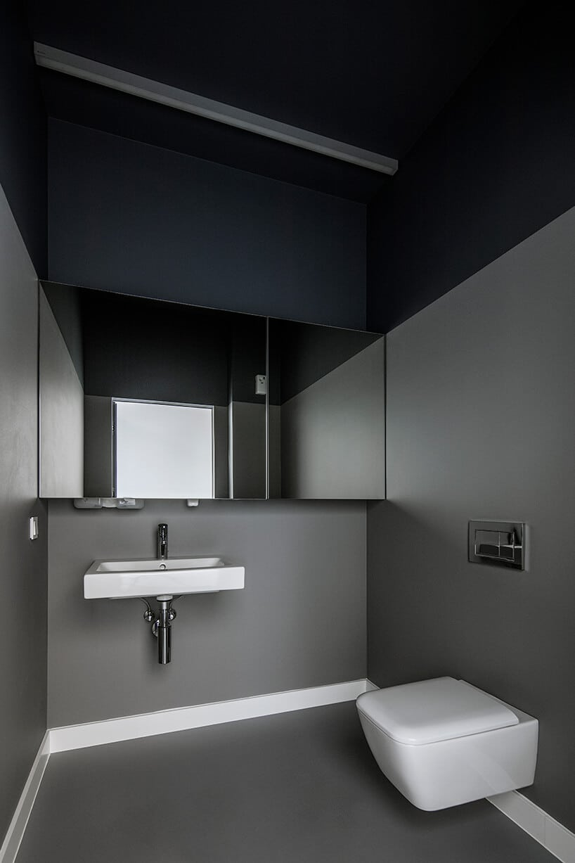 toaleta zszarymi ścianami oraz lustrem