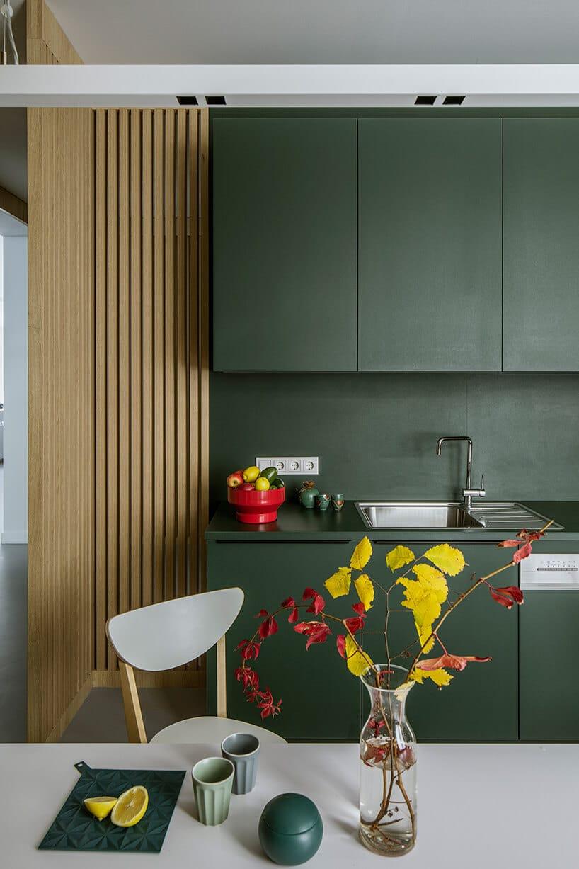 zielona kuchnia zwysokimi szafkami przy drewnianym wykończeniu ściany