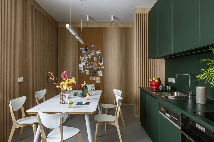 kuchnia wkolorze ciemnej zieleni przy stole zbiałymi krzesłami ikolorowymi elementami