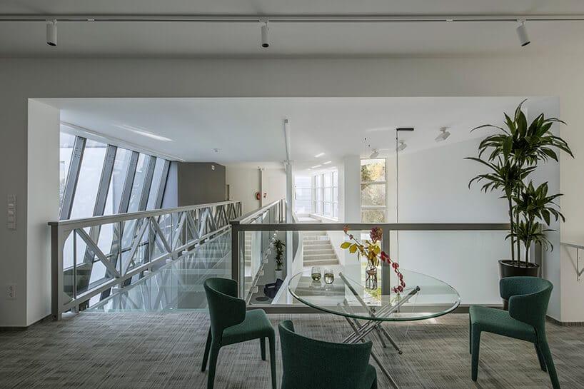 otwarta przestrzeń zpomostem szklanym przy zielonych meszowych zielonych fotelach iszklanym stołem