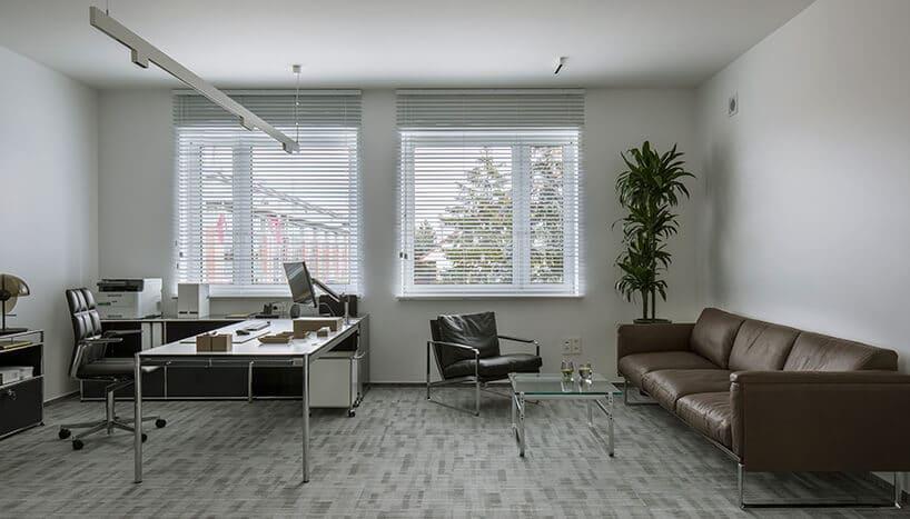 biuro zdużą powierzchnią jasnym wnętrzem ibrązową kanapą