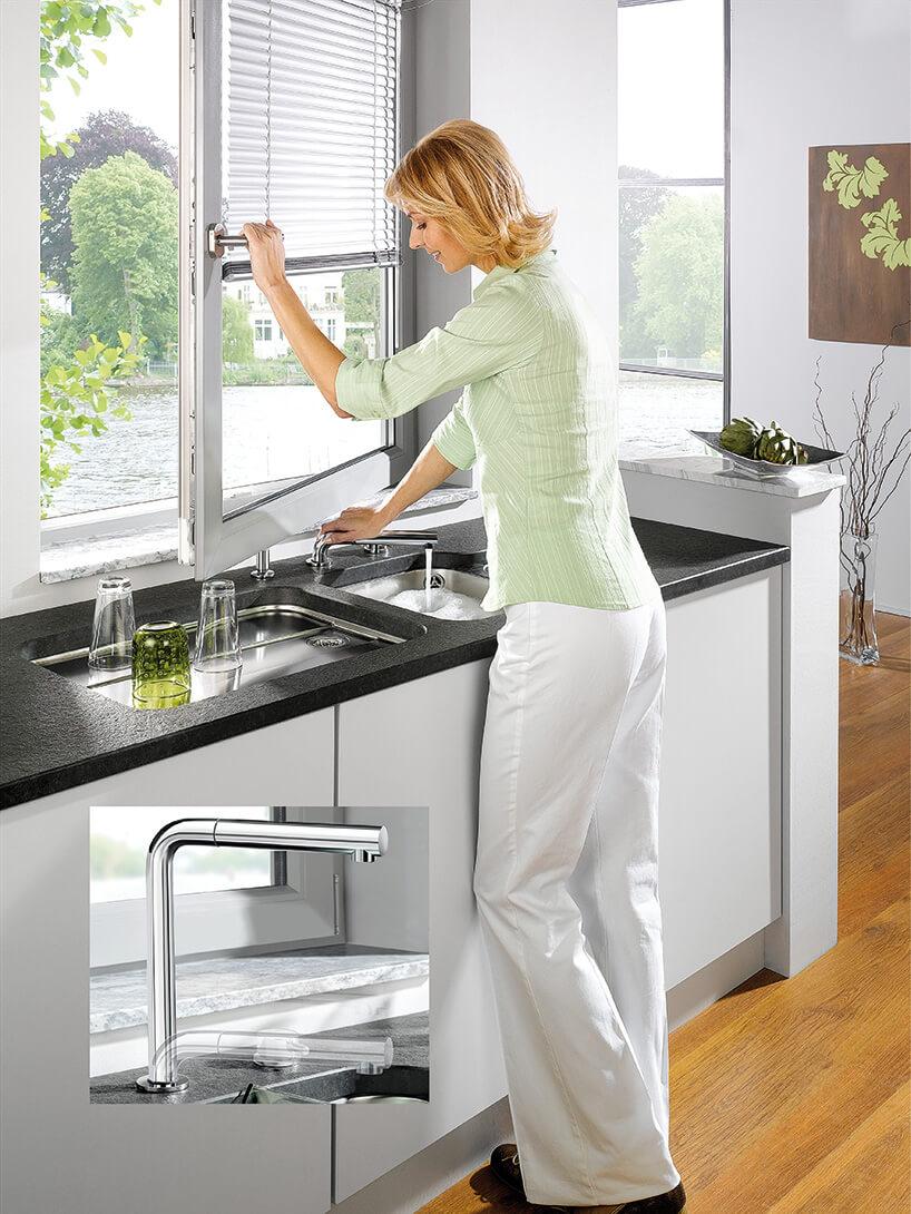 kobieta stojąca przy czarnym blacie kuchennym