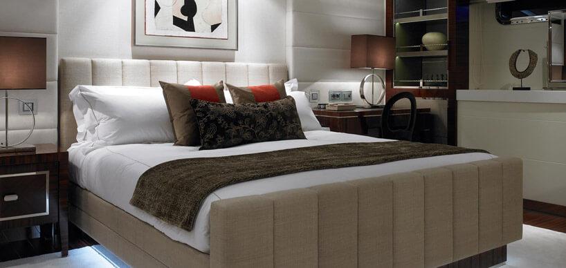łóżko zbiałą pościelą ibrązową narzutą