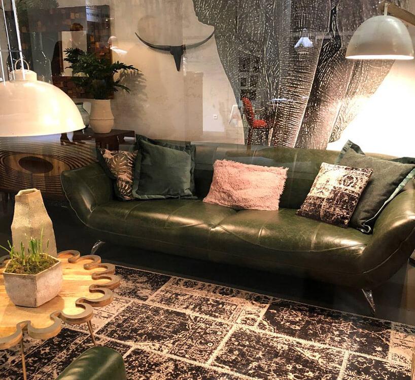 skórzana zielona kanapa wotoczeniu starych mebli