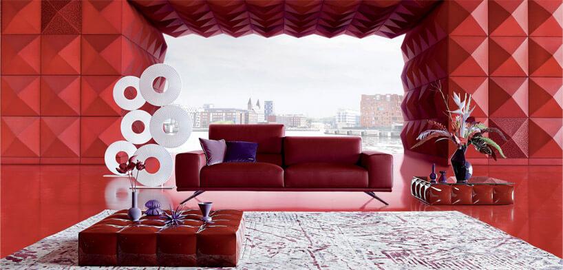 czerwona mała kanapa wpomieszczeniu zczerwonymi panelami we wzory na ścianach