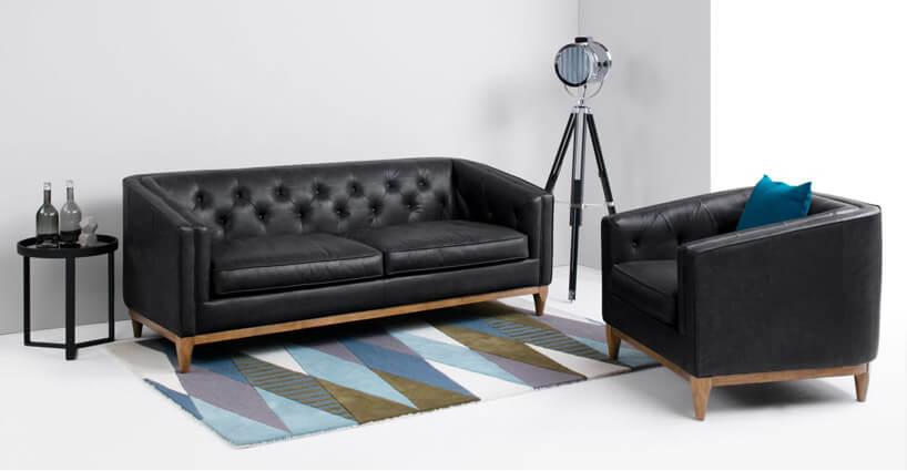czarna pikowana sofa zmałym fotelem przy nowoczesnej lampie