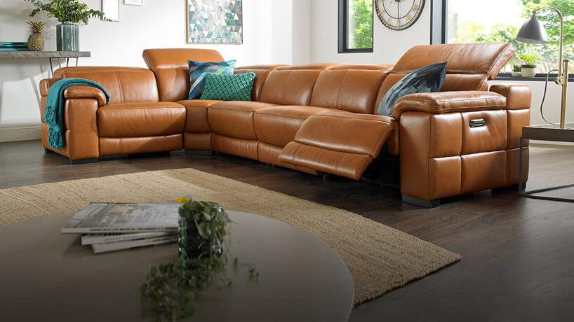 ciemno brązowa kanapa zniebieskimi poduszkami wprzeszklonym salonie