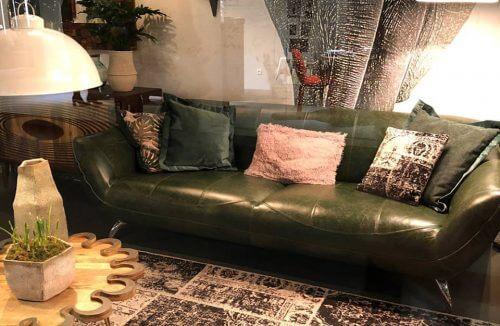 skórzana zielona kanapa w otoczeniu starych mebli