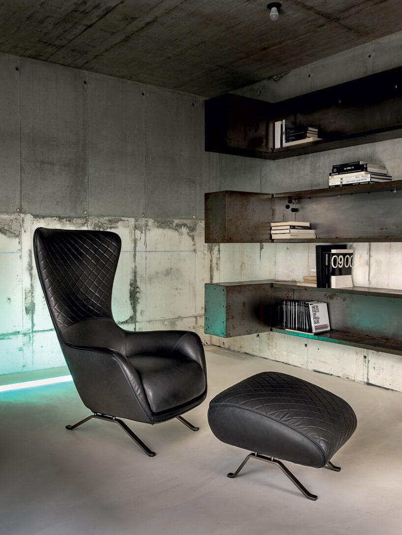 duży czarny skórzany fotel zpodnóżkiem