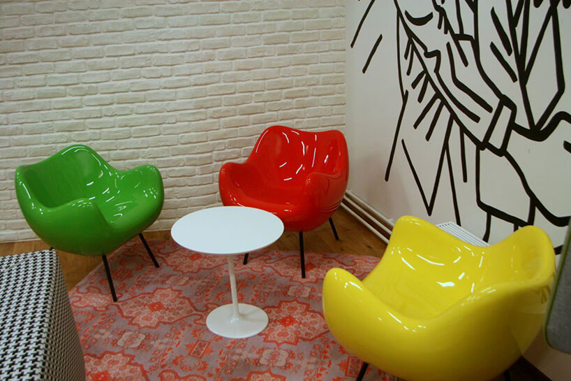 trzy kolorowe fotele przy małym stoliku