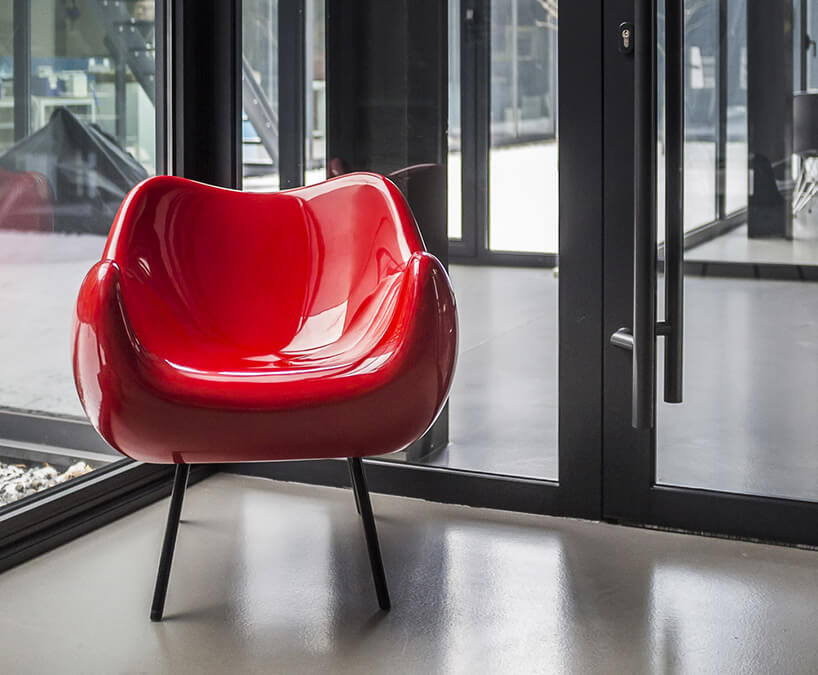 czerwony plastikowy fotel wprzeszklonym wnętrzu