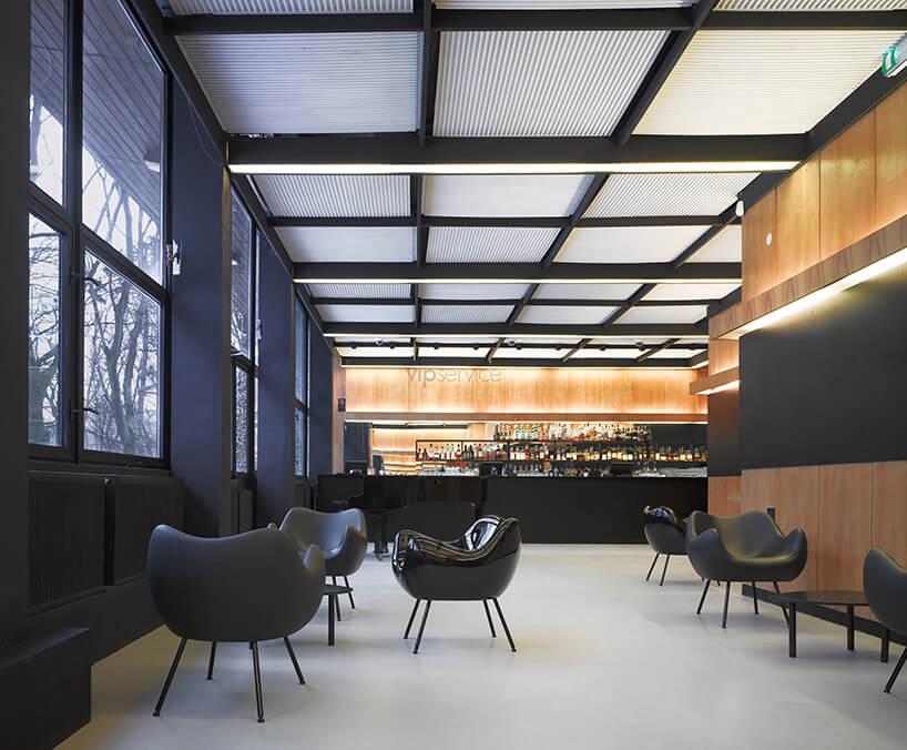 wnętrze restauracji zczarnymi fotelami