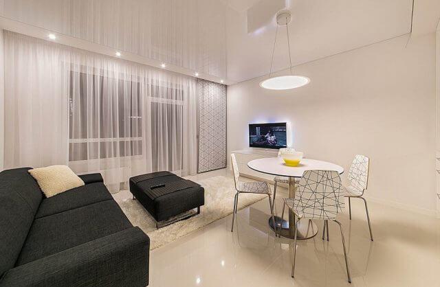 proste białe wnętrze z ciemną sofa