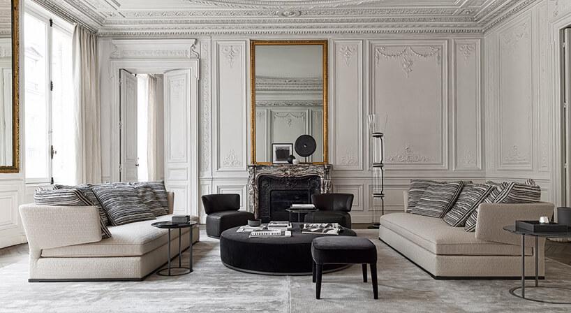 dwie beżowe sofy Amoenus Soft od Maxalto wbiałym salonie bogato zdobionymi ścianami isufitem