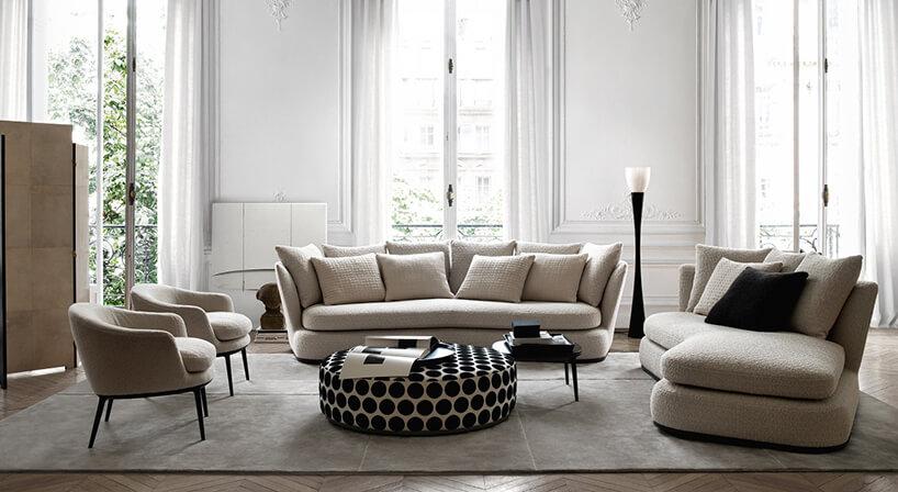beżowa sofa Apollo od Maxalto bez nóżek jak tło dla białego dużego siedziska wczarne kropki na tle wysokich okien