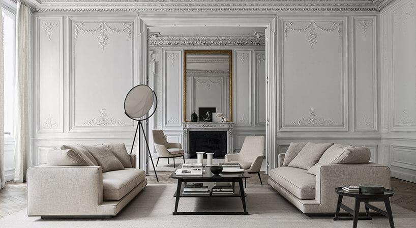 dwie beżowe sofy Aurae od Maxalto wbiałym eleganckim salonie zokrągłym lustrem stojącym na trójnogu