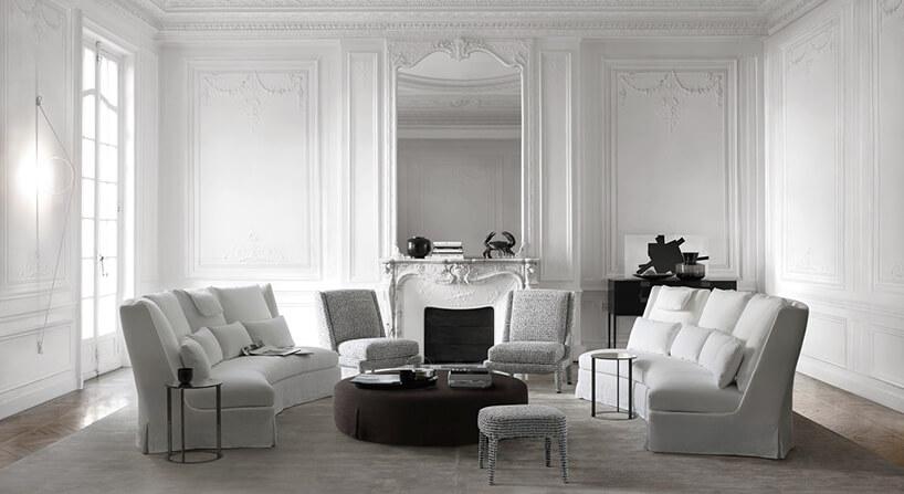 dwie białe sofy Nidus od Maxalto obok dwóch biało czarnych krzeseł na tle białego kominka pod dużym białym lustrem