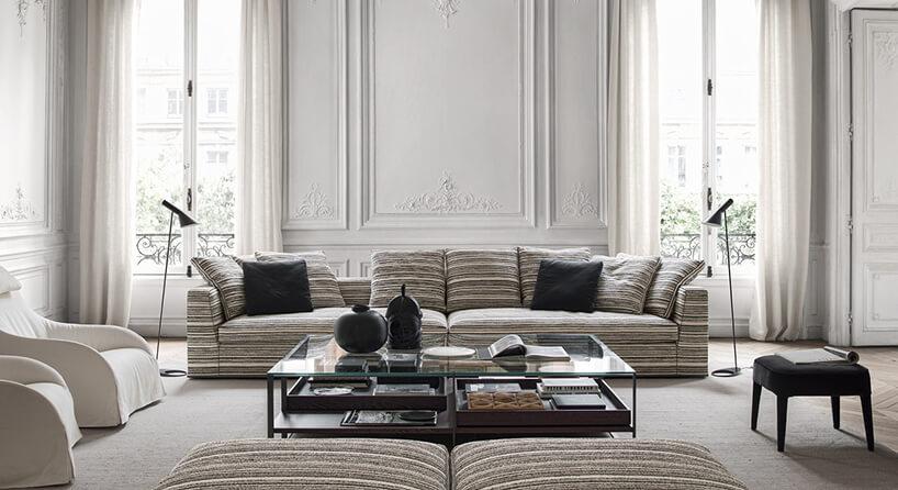 długa sofa Otium Soft Maxalto wkolorowe kreski zpoduszkami na tle zdobionej ściany zwysokimi oknami