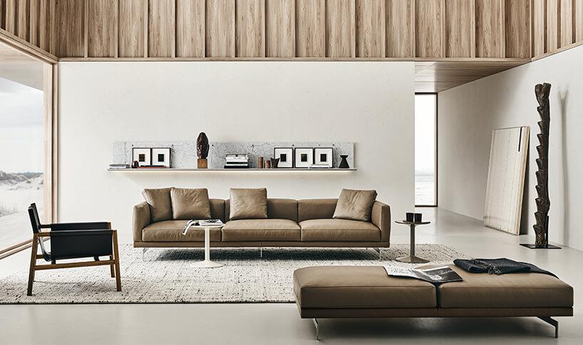 elegancka brązowa skórzana sofa Dock od B&B Italia wjasnym salonie na dużym dywanie