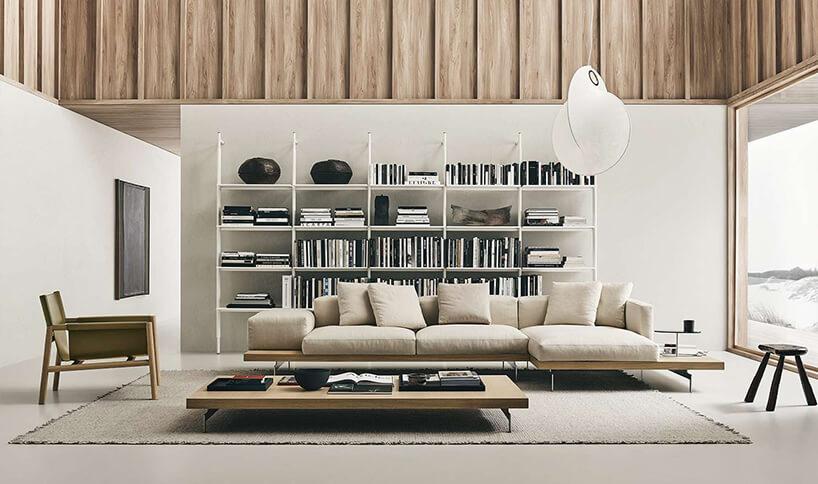 nowoczesna beżowa sofa Dock od B&B Italia na dużej drewnianej ramie zcienkimi metalowymi nogami na tle białej szafki zmetalowych prętów