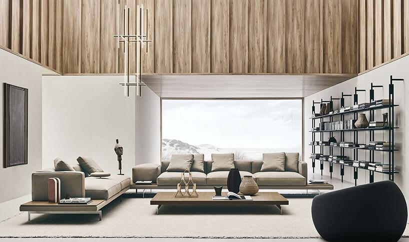 nowoczesna beżowa sofa Dock od B&B Italia zelementem narożnym na tle panoramicznego okna