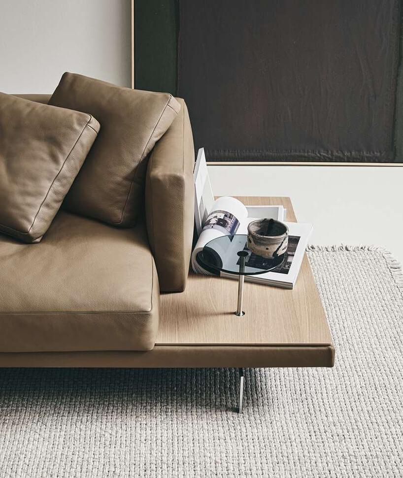 nowoczesna brązowa sofa Dock od B&B Italia ze zbliżeniem na małą szklaną podstawkę wmontowaną wsofę