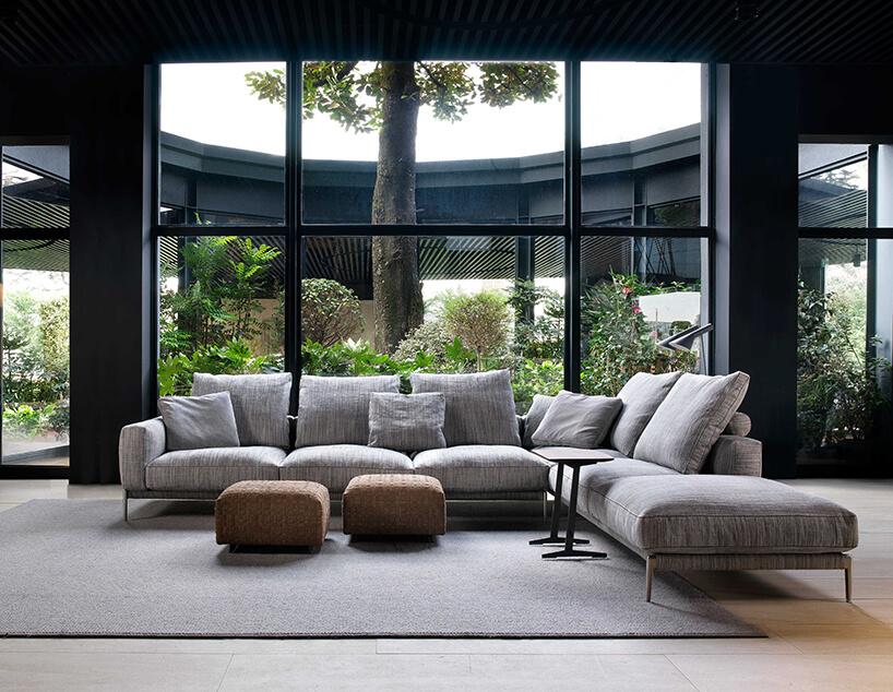 duża wszare paski sofa Romeo od Flexform zelementem narożnym na tle panoramicznych okien na ogród zdużym drzewem