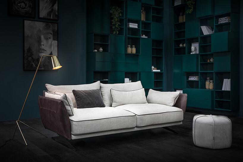 elegancka sofa Monroe Max od MTI Furninova zbeżowym siedziskiem ioparciem ze śliwkowymi bokami na tle zielonej wysokie zabudowy