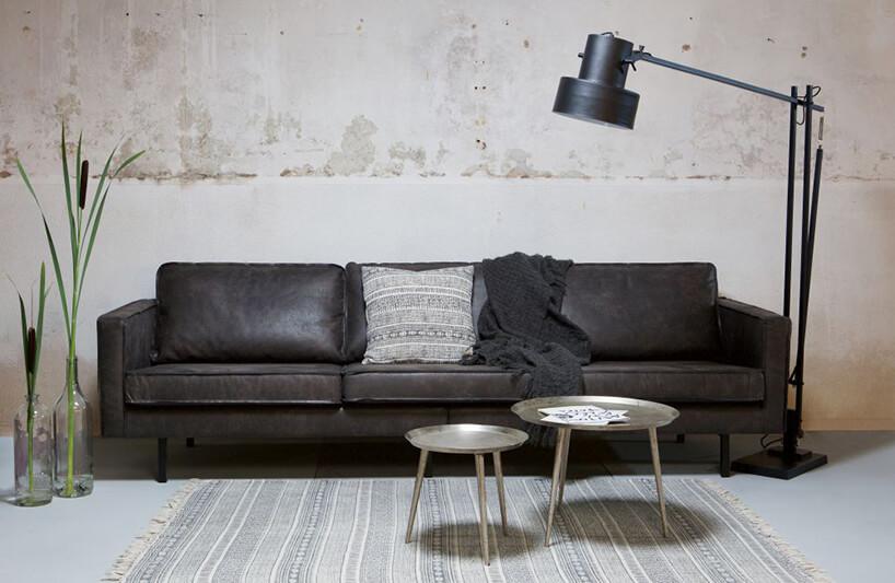 czarna skórzana sofa Rodeo od BE Pure obok duże czarnej lampy na ramieniu na tle szarej ściany